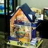 บ้านชายทะเลสีฟ้าเข้ม มีเรือใบและประตูหน้าบ้านเป็นบานกระจกใส
